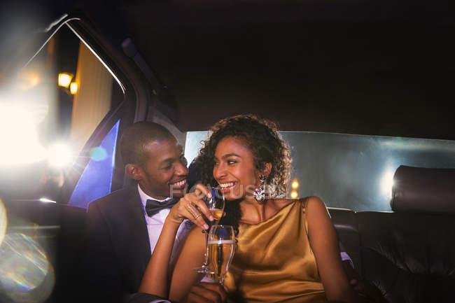 Зоряна пара п'є шампанське всередині лімузин за межами подій — стокове фото