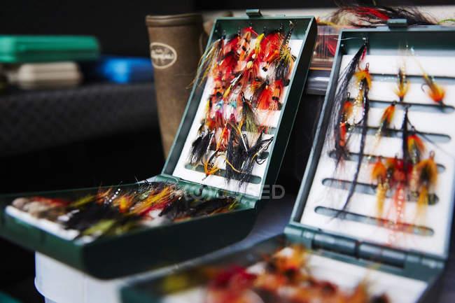 Gancho de pesca con mosca carretes en cajas de trastos - foto de stock