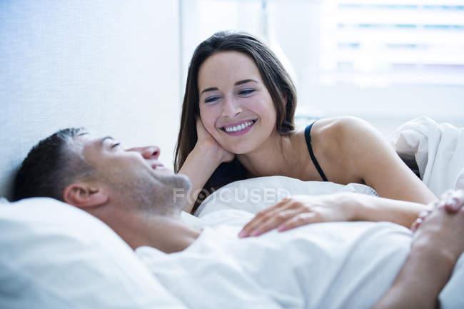 Lächelndes Paar liegt im Bett und redet miteinander — Stockfoto