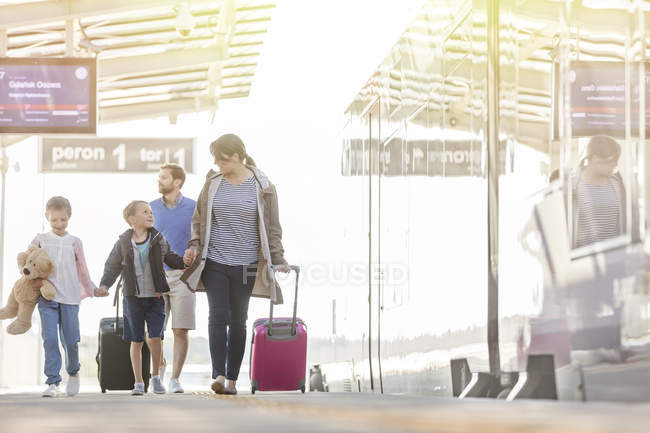 Family walking pulling suitcases in airport concourse — Stock Photo