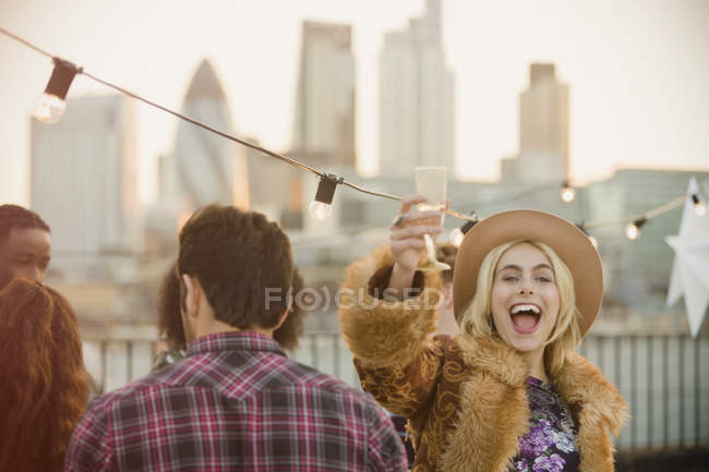 Portrait enthusiastic young woman drinking champagne at rooftop party — Stock Photo