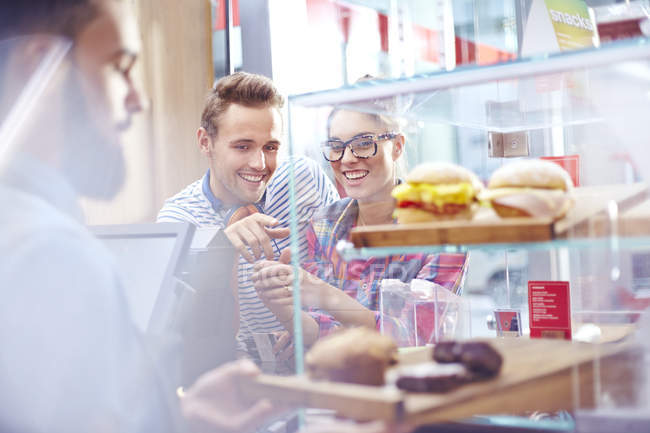 Couple choosing food at display case in cafe — Stock Photo