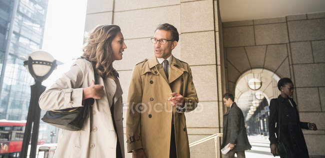 Corporate businessman and businesswoman talking outdoors — Stock Photo