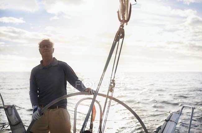 Homem aposentado, vela, vela de direção em leme — Fotografia de Stock