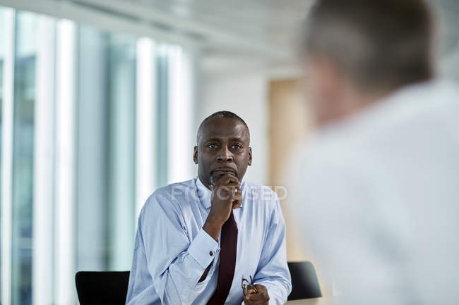 Serious businessman listening to colleague in meeting — Stock Photo