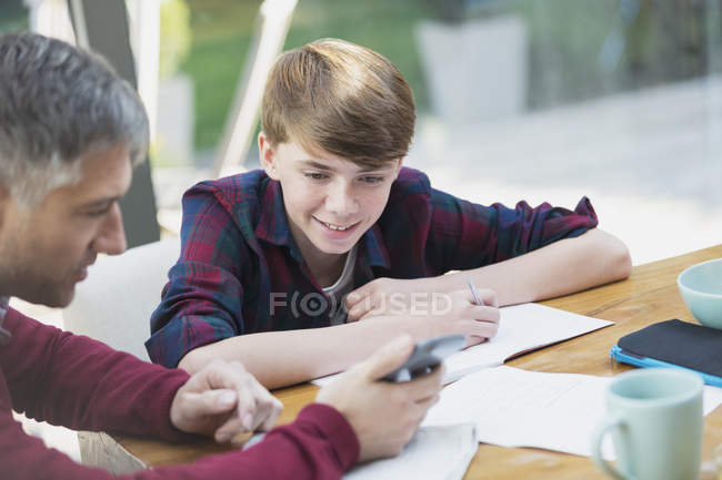 Батько з калькулятор, допомагаючи син з математикою домашніх завдань — стокове фото