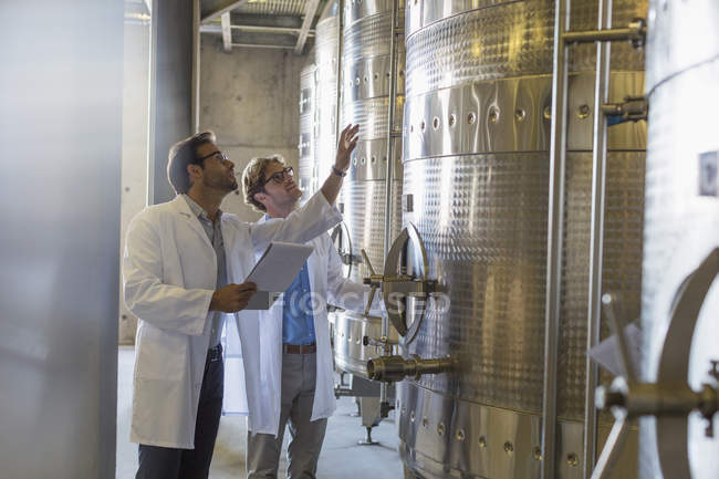 Vintners in lab coats checking vats in winery cellar — Stock Photo
