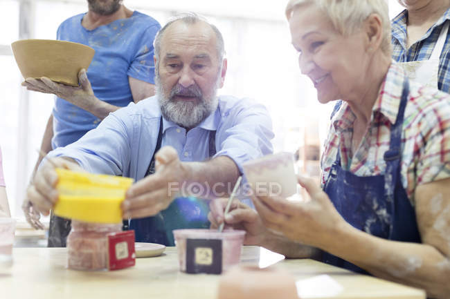 Senior couple painting pottery in studio — Stock Photo