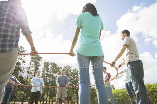 Equipe formando ligação círculo ao redor do aro de plástico — Fotografia de Stock
