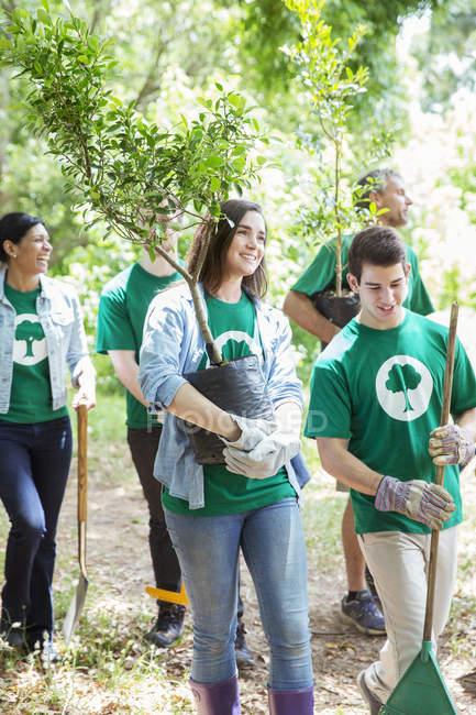 Volontari di ambientalista sorridente piantare albero nuovo — Foto stock