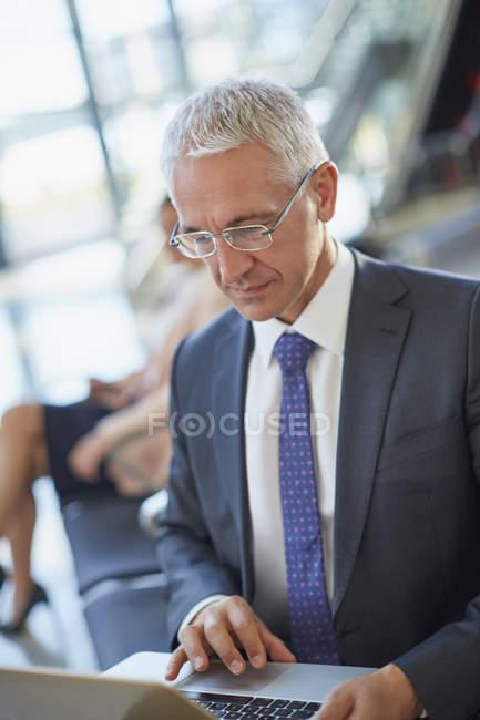 Homme d'affaires travaillant en utilisant un ordinateur portable à l'aéroport — Photo de stock