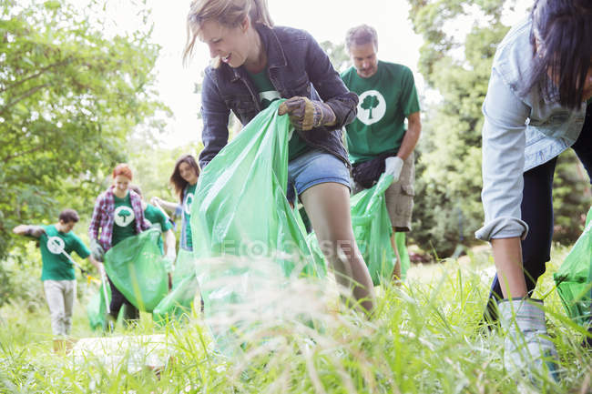 Environmentalist volunteers picking up trash in field — Stock Photo