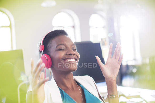Smiling businesswoman listening to music on headphones in office with eyes closed — Stock Photo