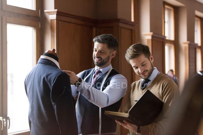 Кравців, вивчаючи костюм і беручи відзначає в магазин чоловічого одягу — стокове фото