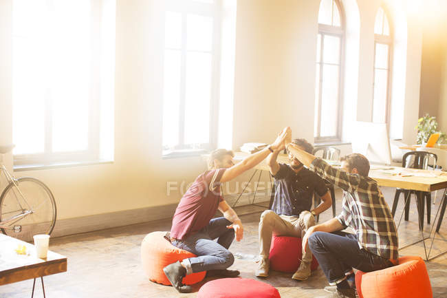 Creative business people joining hands in circle in sunny office — Stock Photo