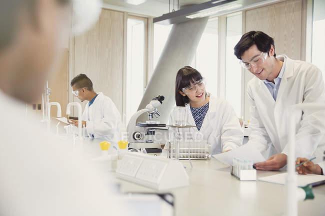 Студенты колледжа проводят научные эксперименты в классе научной лаборатории — стоковое фото