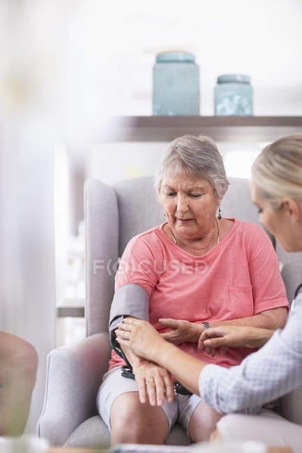 Arzt überprüft Blutdruck bei Seniorin — Stockfoto