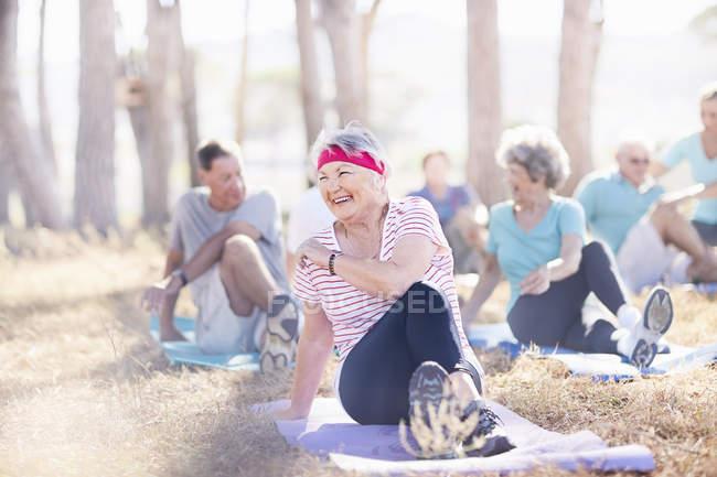 Улыбающаяся пожилая женщина, практикующая йогу в солнечном парке — стоковое фото