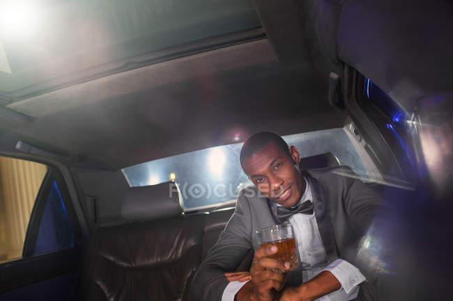 Портрет впевнено знаменитості пити коктейль всередині лімузин за межами подій — стокове фото
