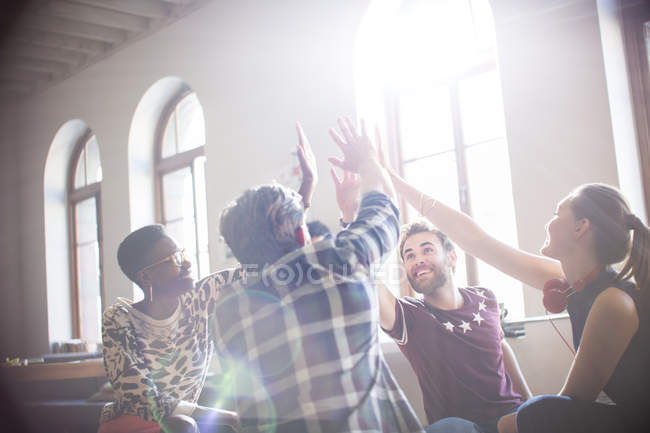 Casual business people raising hands in circle in sunny office meeting — Stock Photo