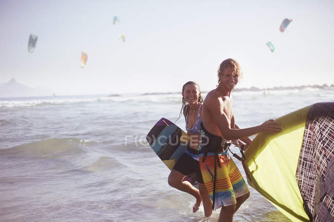 Portrait smiling couple with kiteboarding equipment in ocean surf — Stock Photo
