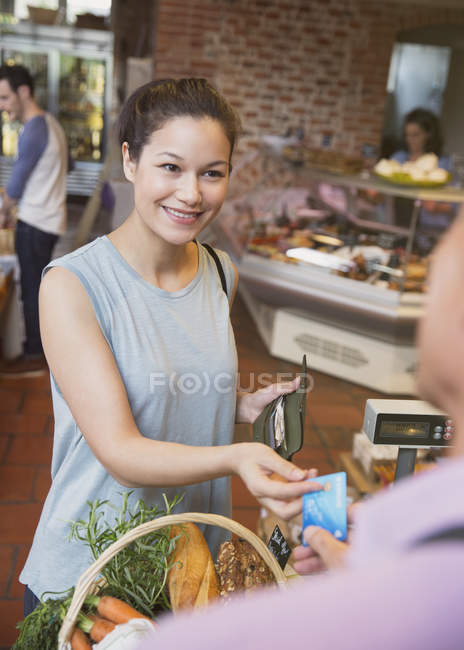 Smiling woman paying with credit card at grocery store checkout — Stock Photo