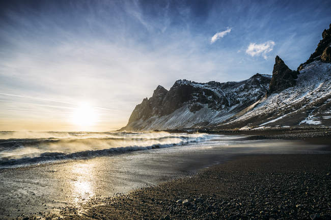 Sun setting over tranquil beach and snowy mountain, Iceland - foto de stock