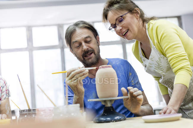 Mature couple painting pottery in studio — Stock Photo