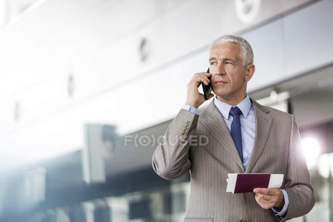Empresário com bilhetes de avião e passaporte falando no celular em aeroporto — Fotografia de Stock