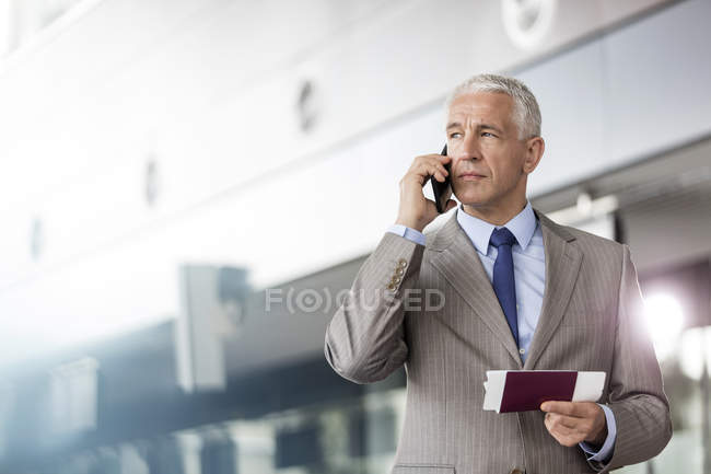 Businessman with passport and airplane ticket talking on cell phone in airport — Stock Photo