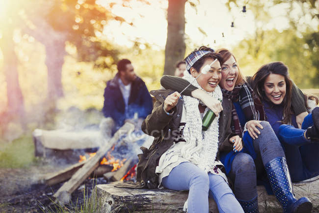 Friends laughing roasting marshmallows at campfire — Stock Photo