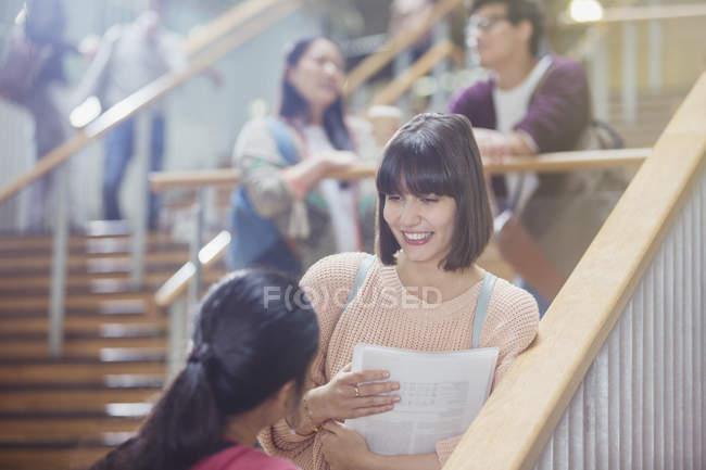 Estudiantes mujeres hablando en la escalera - foto de stock