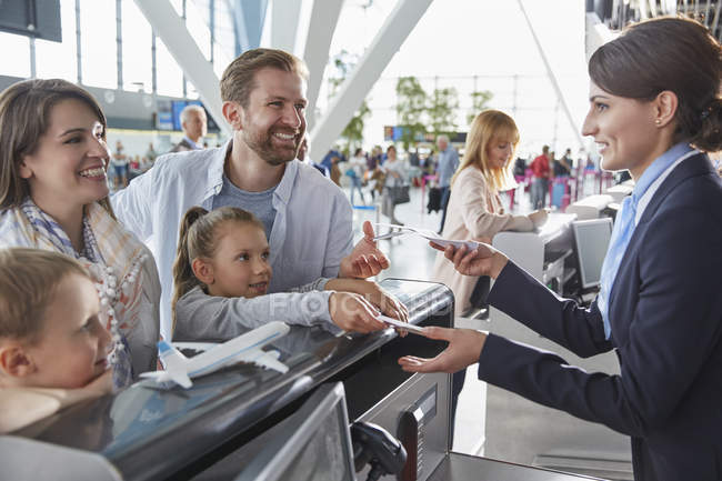 Customer service representative helping family checking in with tickets at airport check-in counter — Stock Photo