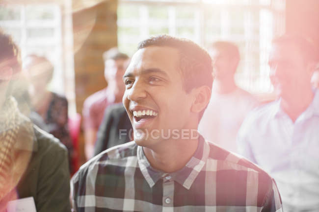Man laughing in audience indoors — Stock Photo