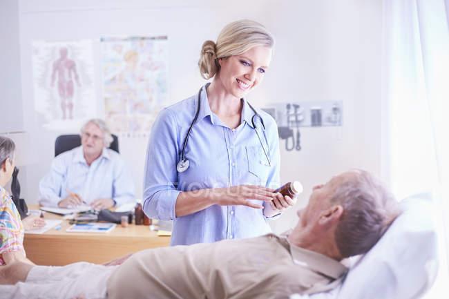 Médico sobre medicación de la prescripción al hombre senior - foto de stock