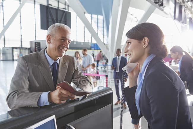 Empresario de ayuda representante de servicio al cliente con el pasaporte en el mostrador de facturación de aeropuerto - foto de stock