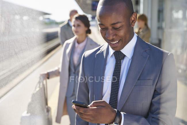 Uomo d'affari che scrive con il cellulare sulla piattaforma della stazione ferroviaria — Foto stock