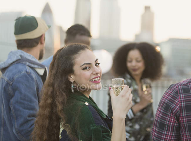 Portrait smiling young woman drinking champagne at rooftop party — Stock Photo