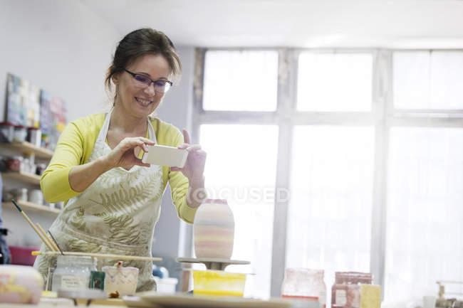 Зріла жінка фотографує Кераміка вази з камери телефону в студії — стокове фото