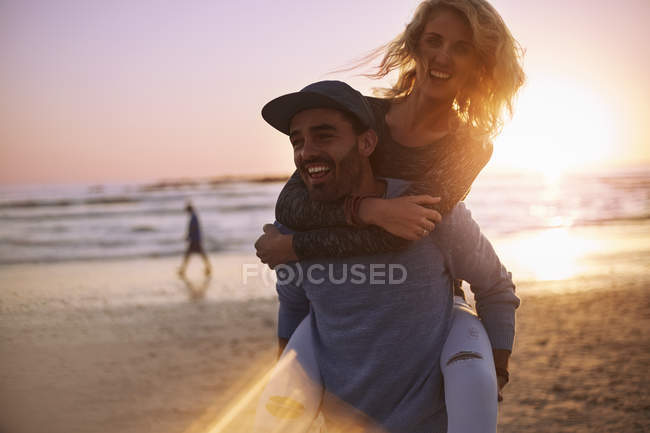 Playful couple piggybacking on sunset beach — Stock Photo