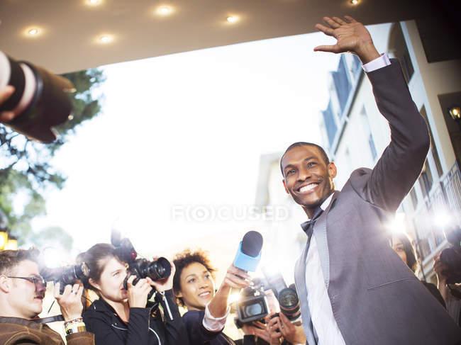 Размахивая знаменитости интервью и сфотографировали папарацци на мероприятии — стоковое фото