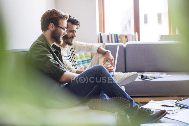 Casual businessmen using laptop on sofa at modern office — Stock Photo