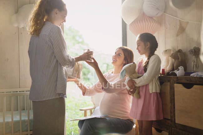 Mujer embarazada recibiendo regalo en la guardería - foto de stock