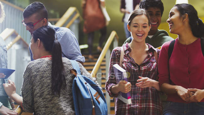Smiling college students together in stairway — Stock Photo