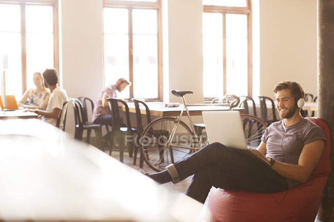 Smiling casual businessman wearing headphones and working at laptop on bean bag chair in office — Stock Photo