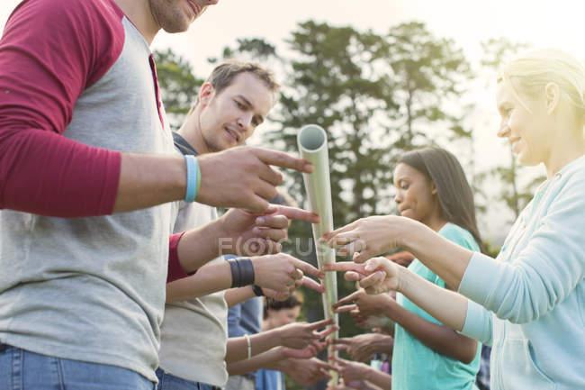 Team balancing pole on fingertips — Stock Photo