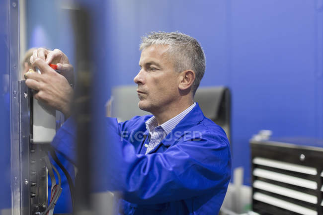 Worker adjusting machinery in steel factory — Stock Photo