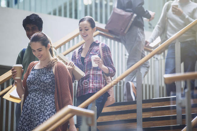 College students with coffee descending stairway — Stock Photo