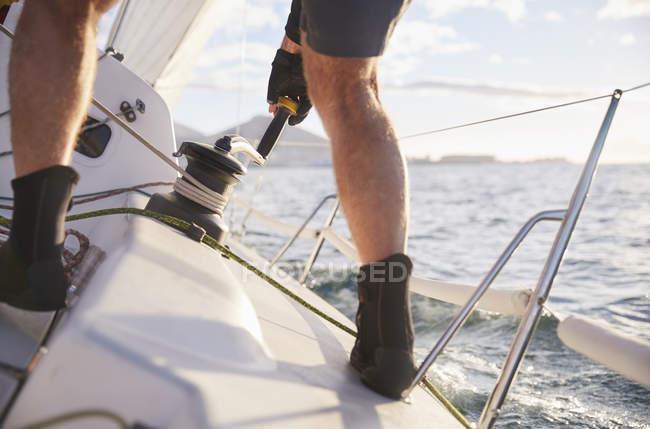 Mann segelt Seilwinde auf abfallendem Segelboot — Stockfoto