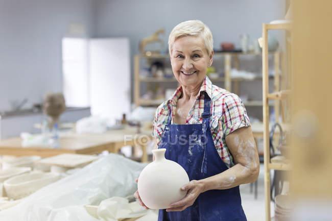 Retrato sonriente senior mujer florero de cerámica en el estudio - foto de stock